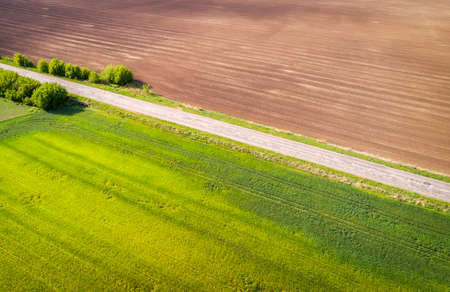 Aerial view of agricultural fields and broken patched road. Natural grass. Imagens - 148480724