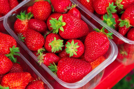 Tasty juicy strawberry berries in boxes, on the market Imagens