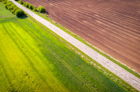 Aerial view of agricultural fields and road. Natural grass. Imagens