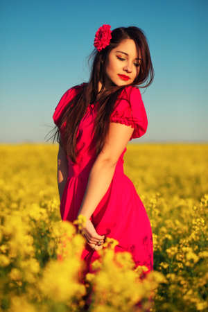 Beautiful young girl in a red dress posing in a field with canola. Happy woman on the nature. Spring season, warm day.
