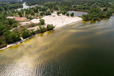 A beach near the city in springtime. Aerial view. Dirty river or lake. Few people. Quarantine