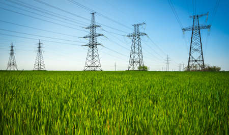 High voltage lines and power pylons in a flat and green agricultural landscape on a sunny day with clouds in the blue sky.