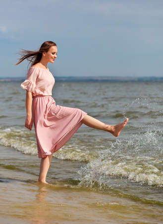Happy woman in a pink dress walking on the coast of the lake and spraying the water with her feet. A joyful girl stands on the beach of the sea and sprays water with her foot. Imagens