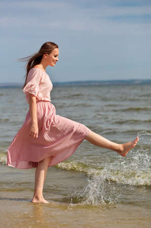 Happy woman in a pink dress walking on the coast of the lake and spraying the water with her feet. A joyful girl stands on the beach of the sea and sprays water with her foot. Stock Photo