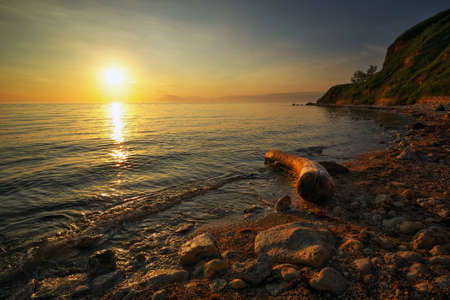 Beautiful landscape with driftwood, sea and sunset sky. Composition of nature Standard-Bild