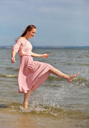 Happy woman in a pink dress walking on the coast of the lake and spraying the water with her feet. A joyful girl stands on the beach of the sea and sprays water with her foot. Standard-Bild