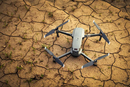 Close-up small drone on brown soil in the field. Flying in the countryside. Stock Photo