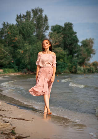 Young girl walking in water by the coastline. Imagens