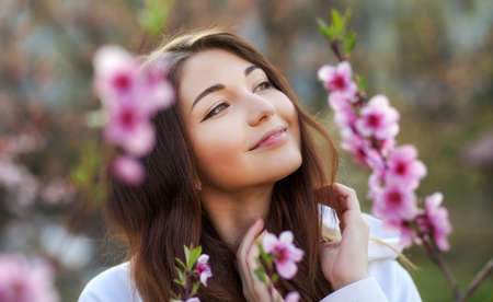 Smiling beautiful girl standing near a peach tree during sunset. Happy face. Spring time. Imagens
