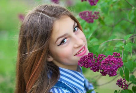 Beautiful young teen girl standing in the flowers of lilac.