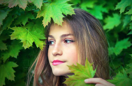 Pretty teen girl among maple leaves, close-up