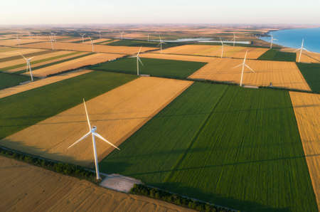 Aerial view of renewable windmills turbines supplying cultivation area with eco power getting energy from wind blowing on vast area of agriculture meadows next to sea. Alternative electricity