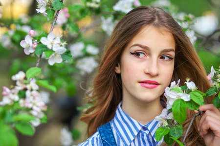 Pretty teen girl are posing in garden near blossom tree with white flowers. Spring time Imagens