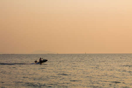 Sunset, jet ski and boat on  the beach bangsaen Thailand