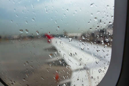 inclement weather: Raindrops on window of aeroplane on parking. Stock Photo