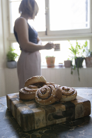 Cinnamon buns with a woman having coffee by the window