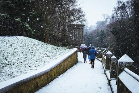 Menschen zu Fuß zum St. Bernard's Well im Schnee, Edinburgh