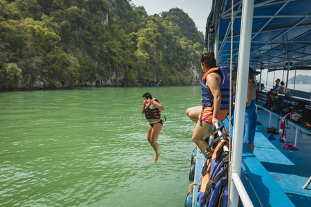 Girl jumping from boat on holiday in Thailand