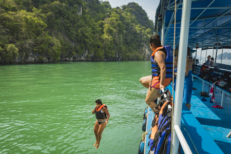 Girl jumping into water from a boat in Thailand 報道画像