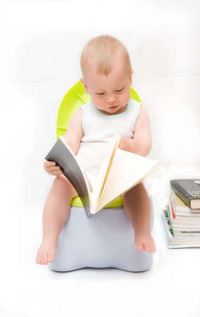 The little boy sits on a chamber-pot and reads the book photo