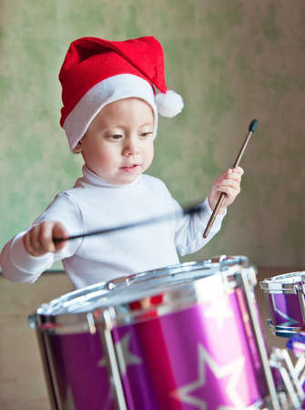 The boy in red cap plays the drums