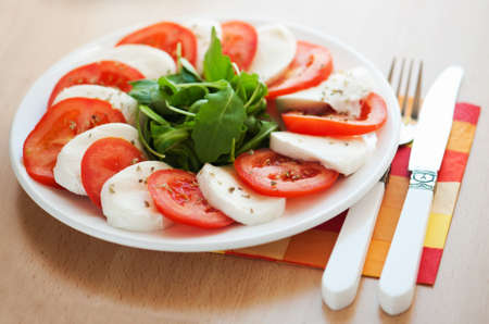 Italian salad with tomatoes and mozzarella with a fork and knife photo