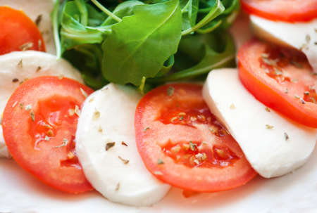 Italian salad with tomatoes and mozzarella filmed in close-up photo