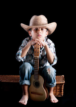 A boy wearing a hat with a guitar on a black background photo