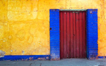 Multi-colored facade of the house with red door Foto de archivo
