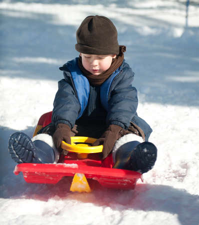 The boy sits on a sled photo