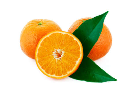 Two whole and one sliced mandarin with green leaves isolated on white background photo