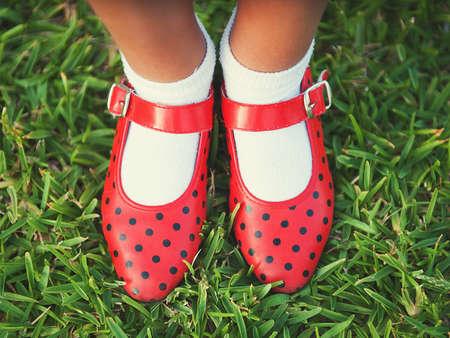 niños danzando: Zapatos rojos con lunares en un fondo de hierba Foto de archivo