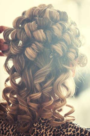 Blonde girl doing a perm hair salon Foto de archivo
