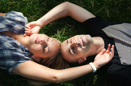 Young couple lying on the grass with eyes closed photo