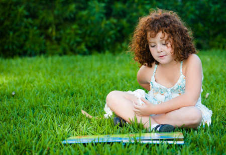 The red-haired girl reading a book in the park photo