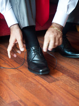 Man tying the laces on black shoes Stock Photo - 17774523