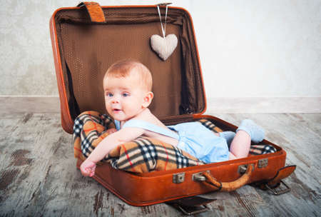 beautiful little boy in the old days a suitcase photo