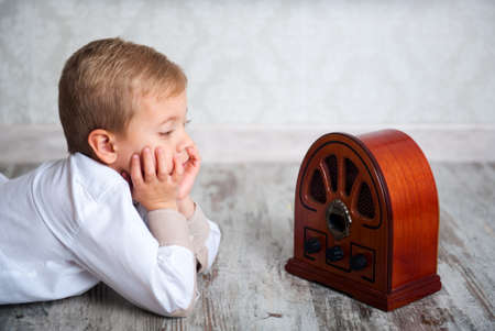 Cute boy of five years listening to Vintage Radio photo