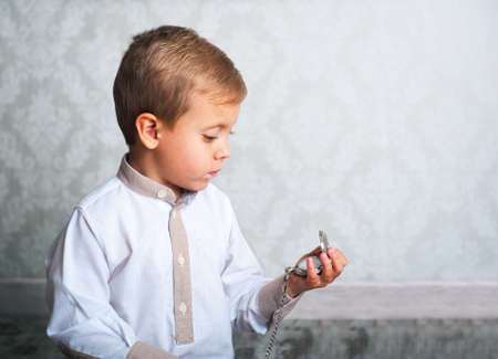 boy with the old clock in the hands of photo