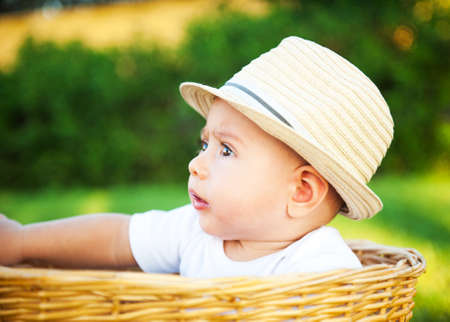 The little boy with a hat in a basket photo