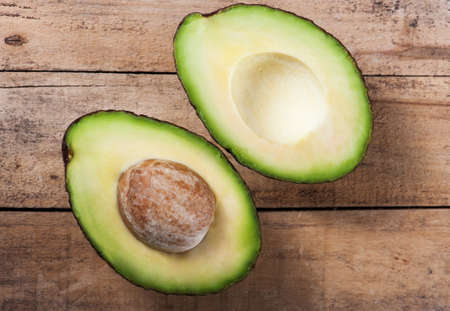 Ripe avocado on a wooden board in the studio photo