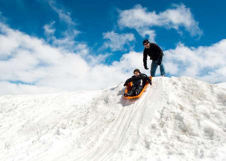 Boy and dad sledding in winter