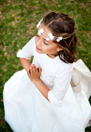 Cute little girl praying on the background of nature