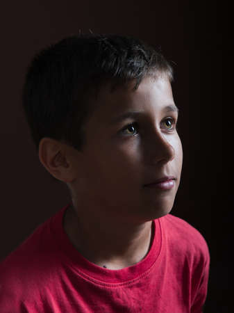 dolorous: young cute boy on a dark background Stock Photo