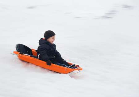 to steer a sledge: A boy rides a sled winter Stock Photo