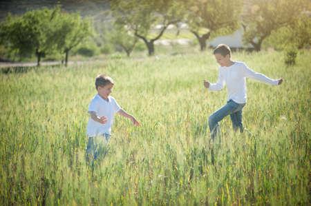 hermanos jugando: Dos hermanos que juegan en un prado en verano