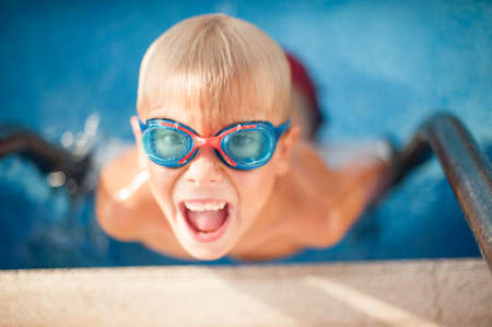 kids activities: Happy boy in glasses of water swims in the pool