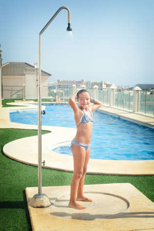 child girl: girl in a bathing suit bathes in a shower by the pool