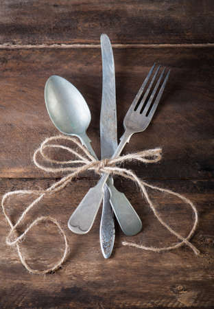 tarnished: old vintage cutlery on a wooden table