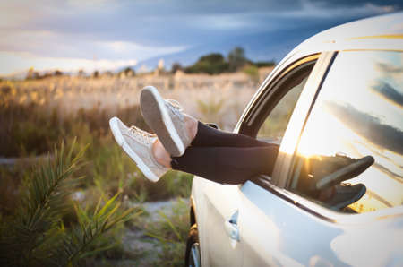 Women's legs out of car window on nature background